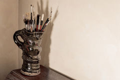 Artists paint brushes in pottery jug. Aged effect. Stock Photos