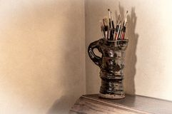 Artists paint brushes in pottery jug. Royalty Free Stock Photos