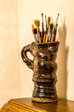 Artists paint brushes in pottery jug. Vintage look. Stock Image