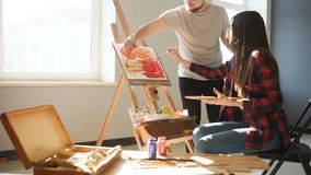 Artists paint pictures in the studio. Creative artists have designed a colorful picture painted on canvas with oil stock video footage