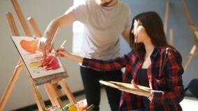 Artists paint pictures in the studio. Creative artists have designed a colorful picture painted on canvas with oil stock video