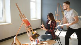 Artists paint pictures in the studio. Creative artists have designed a colorful picture painted on canvas with oil stock footage
