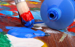 Artists paintbrush and paint. Classic artists palette and blue paint tube with paintbrush dipped in red and blue paint Royalty Free Stock Images