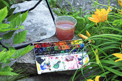 Artists  paints box in garden. Paints water-colors bow in garden Royalty Free Stock Photography