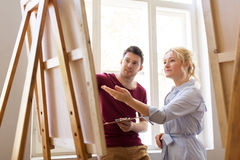 Artists with palette and easel at art school. Creativity, education and people concept - men artist or student with palette and teacher painting on easel at art Stock Images