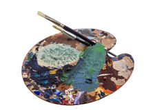Artists palette. Paint covered artists palette with 2  brushes Royalty Free Stock Photography