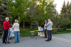 Artists with pictures of people at easels in the city park offer to draw a portrait to passersby on a warm clear day against the royalty free stock images