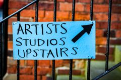 Artists Studio sign. Hand drawn artists studio sign attached to railings pointing up with brick wall in the back ground Royalty Free Stock Photography