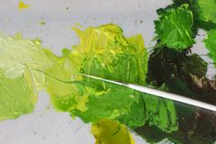 Artists white brush and green acrylic oil paints on artistic palette. Macro artist`s palette, texture mixed oil paints in different green colors and saturation stock illustration