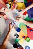 Artists wooden table with paints and colored paper. Art and artwork concept. Hands hold colorful markers and draw. Markers in male and female hands draw cute stock photos