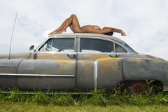Artitistic Nude Female Woman on Old Retro Vintage Cadillac Royalty Free Stock Images