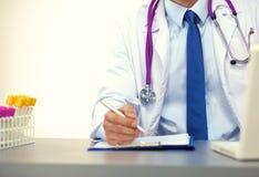 Arts bij zijn bureau die met medische apparatuur op de achtergrond werken Royalty-vrije Stock Fotografie