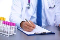 Arts bij zijn bureau die met medische apparatuur op de achtergrond werken Royalty-vrije Stock Foto's