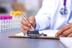 Arts bij zijn bureau die met medische apparatuur op de achtergrond werken Stock Afbeelding