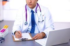 Arts bij zijn bureau die met medische apparatuur op de achtergrond werken Royalty-vrije Stock Afbeelding