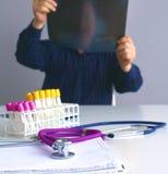 Arts bij zijn bureau die met medische apparatuur op de achtergrond werken Stock Afbeeldingen
