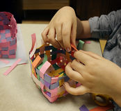Arts And Crafts. With the hands of a child crafting a basket made of construction paper as a symbol of art education at schools or other creative activities for Stock Images