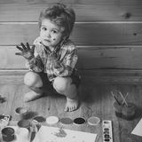 Arts and crafts. Boy painter painting on wooden floor. Imagination, creativity and freedom concept. Child with colored hands, gouache paints and drawings. Kid stock photos