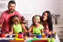 Arts and crafts. Girls painters painting with mother and father. Entertainment, cosplay party and holiday. Learning and playing concept. Happy family showing stock photos