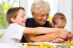 Arts and crafts. Grandmother with grandchildren applying a dry maple leaves using glue while doing arts and crafts Stock Photo