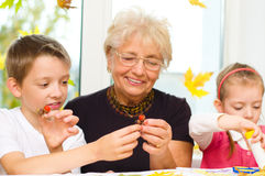 Arts and crafts. Grandmother with grandchildren applying a dry maple leaves using glue while doing arts and crafts Royalty Free Stock Image