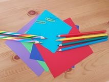 Arts and Crafts Supply, Kids Crafts, Back To School, School Supplies. Colored craft paper with colored pencils laying on a wooden background, Art teacher, Craft royalty free stock photo