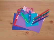 Arts and Crafts Supply, Kids Crafts, Back To School, School Supplies. Colored craft paper with colored pencils laying on a wooden background, Art teacher, Craft royalty free stock image