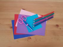 Arts and Crafts Supply, Kids Crafts, Back To School, School Supplies. Colored craft paper with colored pencils laying on a wooden background, Art teacher, Craft royalty free stock images