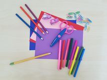 Arts and Crafts Supply, Kids Crafts, Back To School, School Supplies. Colored craft paper with colored pencils, scissor and markers laying on a white background royalty free stock photos