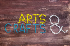 "Arts & Crafts. ""Arts & Crafts"" written with beads on a wooden background Stock Photos"