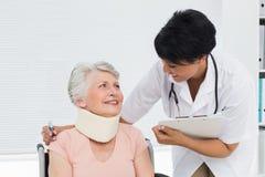 Arts die aan een hogere patiënt met cervicale kraag spreken stock fotografie