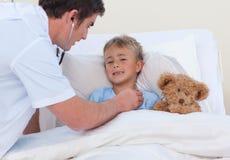 Arts die aan een kind luistert breaht Stock Afbeeldingen