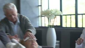 Arts die aan een ziek bejaarde en haar echtgenoot thuis spreken stock videobeelden