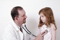 Arts die aan het hart van het kind luistert Stock Foto
