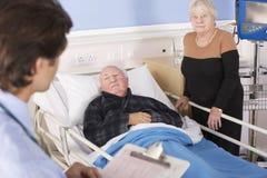 Arts die aan hoger paar in het ziekenhuis spreekt stock foto