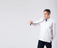 Arts die aan lege exemplaarruimte luisteren met stethoscoop Stock Foto's