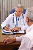 Arts die aan patiënt en nemende nota's luisteren Royalty-vrije Stock Foto