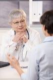 Arts die aan patiënt luistert Stock Foto