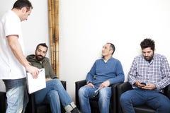 Arts die aan patiënt in wachtkamer spreken Stock Afbeeldingen