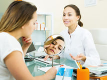 Arts die aan vrouwelijke bezoeker in esthetisch geneeskundecentrum spreken royalty-vrije stock afbeelding