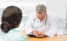 Arts die aan zijn patiënt luisteren en nota's nemen Stock Fotografie