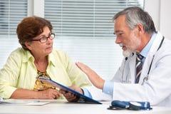 Arts die aan zijn vrouwelijke patiënt spreken Royalty-vrije Stock Foto's