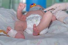 Arts die auscultatie pasgeboren baby met orthopedische kraag, de sensor van impulsoximeter en fopspeen in intensive careeenheid b stock foto