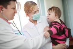 Arts die baby onderzoekt stock afbeeldingen