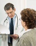 Arts die Bevindingen bespreekt met Patiënt Stock Afbeeldingen