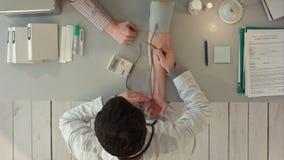 Arts die bloeddruk van een patiënt meten bovenkant stock video