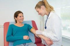 Arts die bloedonderzoek aangaande vrouwelijke patiënt doen stock foto's