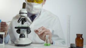 Arts die chemisch element in laboratorium bestuderen die een microscoop gebruiken stock footage