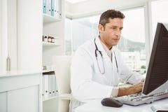 Arts die computer met behulp van op medisch kantoor Stock Afbeeldingen