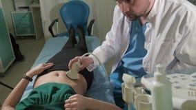 Arts die 3d ultrasone klank op buik van t-vrouw in kliniek 4k doen stock videobeelden